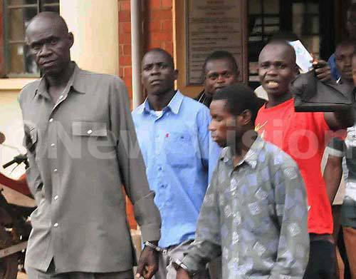 ASP. Charles Oriku (left) wears a resigned expression as he heads to jail with other suspects on Tuesday.