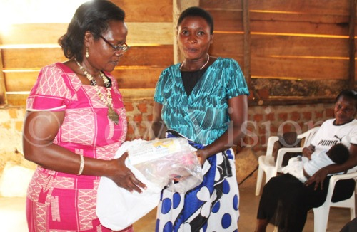 Eleanor Bageine (L) giving Angela Tindimwebwa a mama kit after the training on importance of antenatal care.