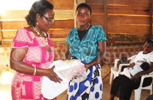 Eleanor Bageine (L) giving Angela Tindimwebwa a mama kit after the training on importance of antenatal care.