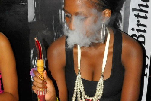A woman smokes shisha in a Kampala hangout recently. A new Bill has been tabled, which among other things, seeks to ban the smoking of shisha.