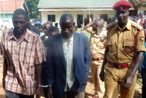 The OC Kalisizo Prison, Mr William Ochow (R) escorts the suspects to prison after they were remanded on murder charges.