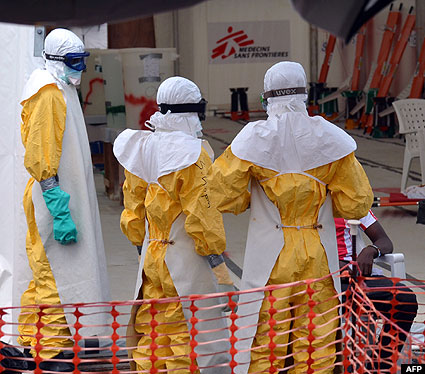 Health workers wearing Personal Protective Equipments (PPE) stand at an Ebola treatment center in Monrovia, Liberia