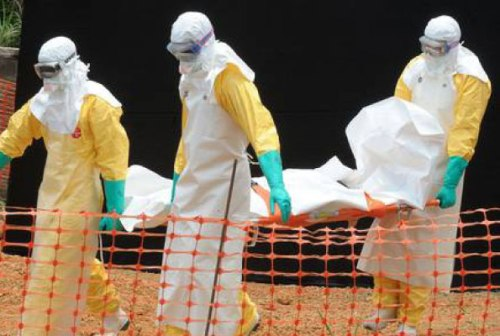 Staff of Médecins sans frontière' carry the body of a person killed by Ebola at a treatment centre in Guinea.