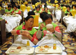 Participants try to break the Guinness World Record for the most people having breakfast in bed, at  …