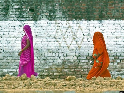 Residents return after defecating in an open field in a village in the Badaun district