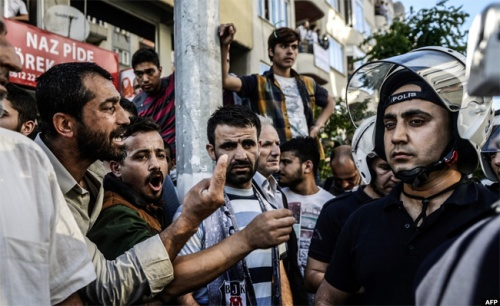 Turkish men shout at a riot police officer as they clash with police during a demonsration