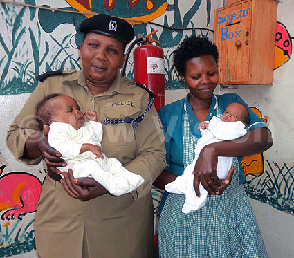 From left, Rebbeca Araba the in-charge Child and Family Protection Unit at Old Kampala Police and a worker of Sanyu Babies carrying the Karamojong twins before one of them passed away