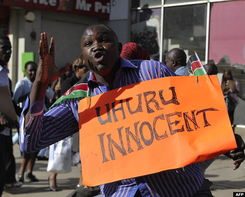A supporter of President Uhuru Kenyatta celebrates in the streets of Nairobi following the ICC ruling to crimes against humanity charges against him on Friday