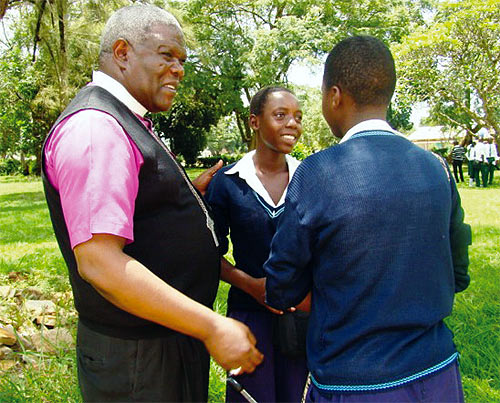 Bishop Kisekka chatting with students after a service at Luwero SS in 2013. Luwero Christians claim Kisekka is influencing the process of identifying a new Bishop