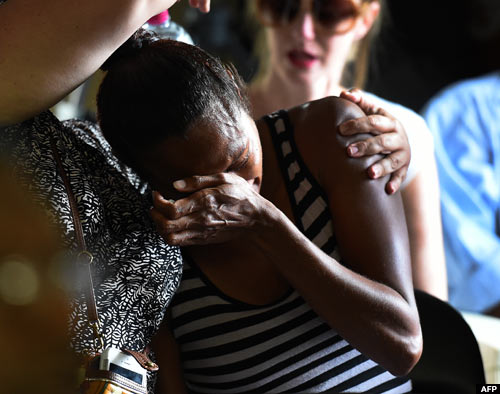 A woman reacts during a church service to remember eight children who were killed by their mother in the Cairns suburb of Manoora