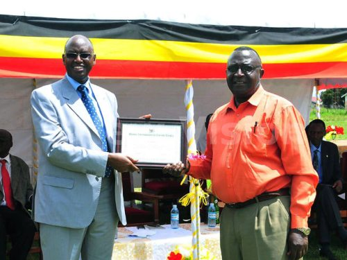 Minister Rwamirama hands over a Certificate to Dr Abbas Kakembo in recognition for his efforts in the fight against tsetse flies. This took place at the Dokolo launch.