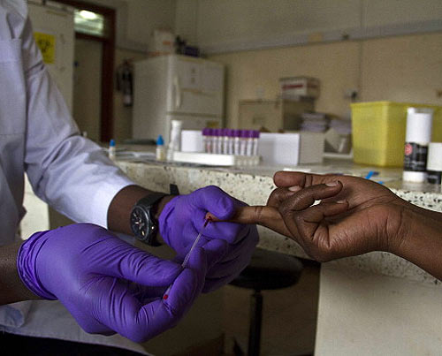 A lab technician draws blood from a patient for HIV testing at the Aids Information Centre in Kampala. (AFP/Getty Images)