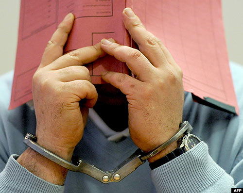The handcuffed ex-nurse covers his face with a folder in a courtroom of the regional court in Oldenburg, northern Germany
