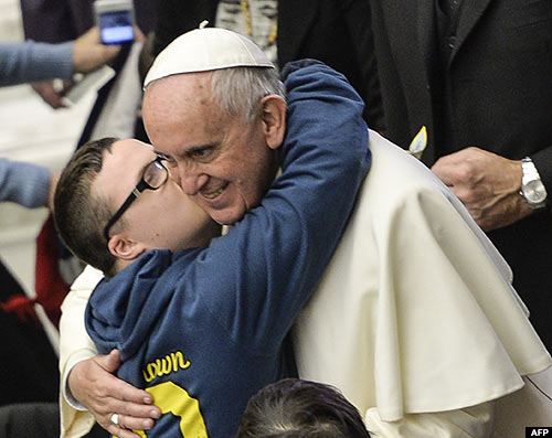 Pope Francis kisses a sick child during his weekly general audience at the Aula Paolo VI hall at the Vatican on Wednesday