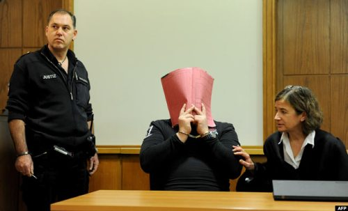 The former nurse, hiding his face, was charged with multiple murder and attempted murder of patients