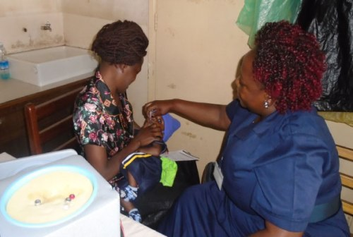 A nurse administers a Tetanus vaccine to an infant. Even adults should be vaccinated against the disease.