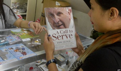 A customer buys a book on Pope Francis at a shop selling Catholic merchandise in Manila