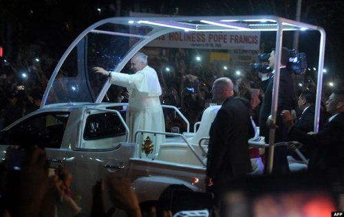 Pope Francis waved to well-wishers as he arrived in Manila on Thursday