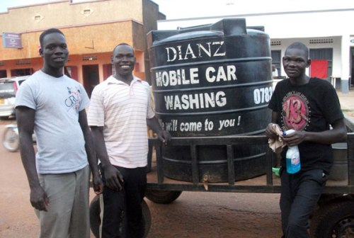 Denis Akera (C) with some of his employees. He started his mobile car wash after Senior Six and is still at it after completing university two years ago. He advises current graduates to create their own jobs.