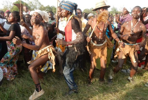 Traditional dancers from Zeu Sub-county display their Agwara dance skills during the Alur community cultural gala in Arua Town recently. Below (R), the dancers blow the Agwara. Below (L), residents join the dancers.