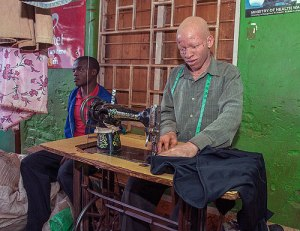 A Malawian albino tailor Henry Bauti (R) works on March 21, 2015 as a customer waits at the Mitundu Trading Center in a suburb of Lilongwe. AFP PHOTO / AMOS GUMULIRA