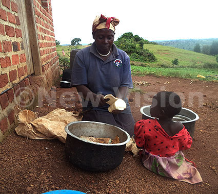 Nyirabakonze peels cassava to prepare a meal for the family.