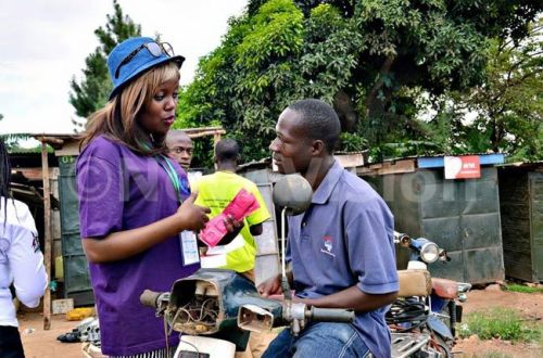 A youth talks to a boda boda (motorcycle) rider about condom use.
