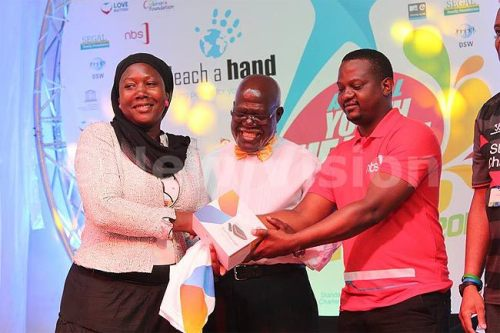 Maj. Rubaramira Ruranga and NBS TV's Joe Kigozi hand over a prize to a participant