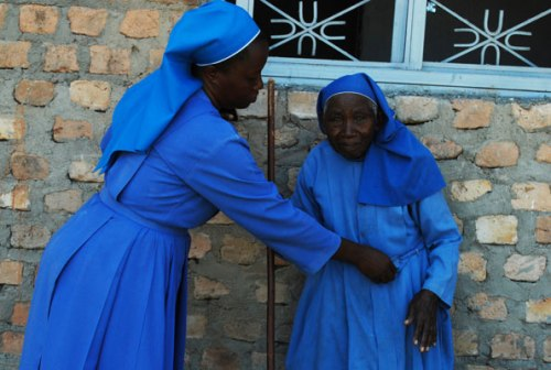 Sister Betty Nalubega, the congregation treasurer, assists Sister Donozio, an aged and weak nun.