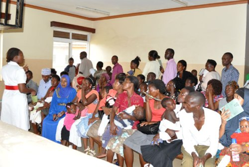 Patients wait to be attended to at Kisenyi Health Centre as a nurse calls for some order in the waiting room.