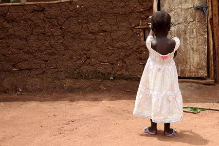 A three-year-old girl who was offered for international adoption without her family's knowledge walks at her grandmother's home in rural Uganda, April 14, 2015.    REUTERS/Katy Migiro