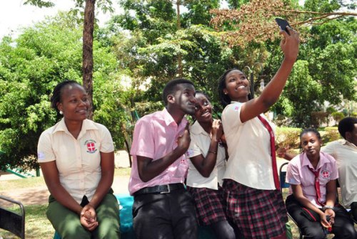 Students of Vienna College Namugongo take a selfie at school using a mobile phone. There has been a raging debate on whether it is right for students to carry mobile phones to school.