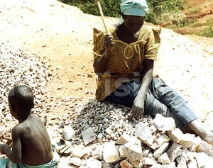 A woman working at a stone-quarrying site alongside her son.