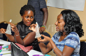 Participants examining the female condoms during media and sexuality training at Eureka Place Hotel in Kampala on Friday Sept 4, 2015.