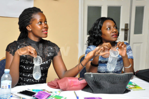 Participants holding female condoms during media and sexuality training at Eureka Place Hotel in Kampala on Friday Sept 4, 2015.