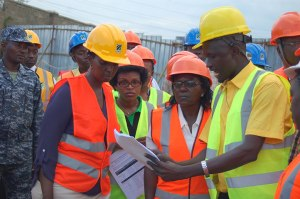 Unra executive director Allen Kagina (L) looking at the work plan shown by Jinja bridge project engineer Michael Ochola