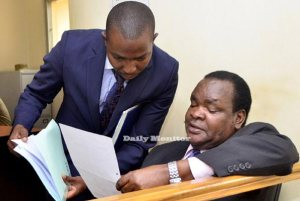 David Oloka (R) consults with his lawyer Nathan Osinde at a recent court session at the Anti-Corruption Court in Kampala. b